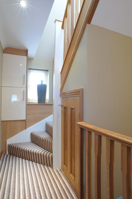 small oak cupboard under loft conversion stairs is ideal use of space